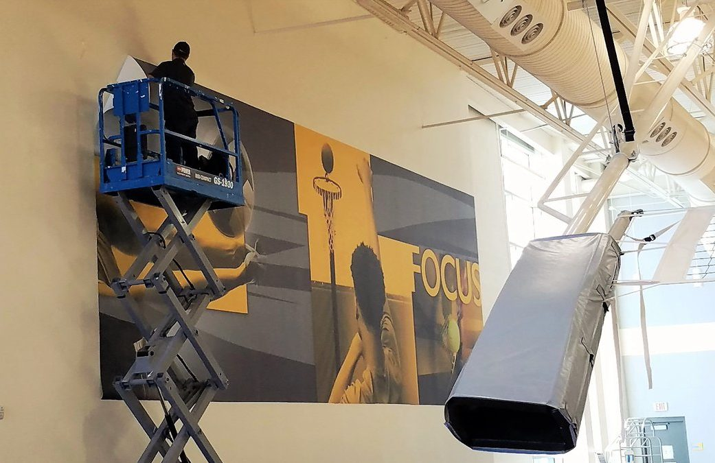 A man on a scissor jack installs a large vinyl wall graphic in a gym.