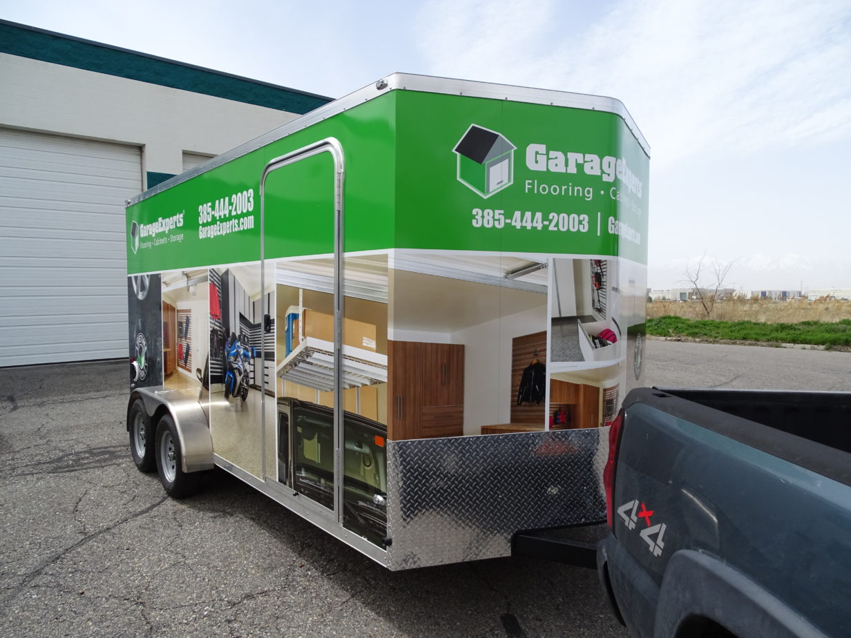 Truck trailer wrapped on all sides with advertisements printed on vinyl.