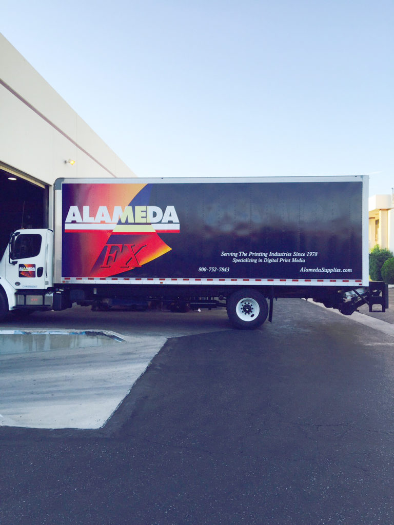 A box truck with a large vinyl graphic applied to the side.
