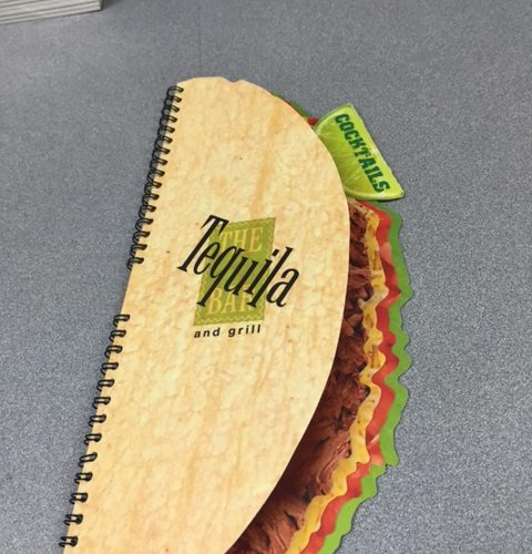 A coil bound menu with pages printed and cut to make the menu look like a taco.