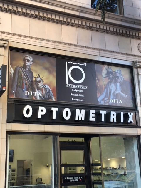 Adhesive vinyl window graphics installed above an optometry shop.